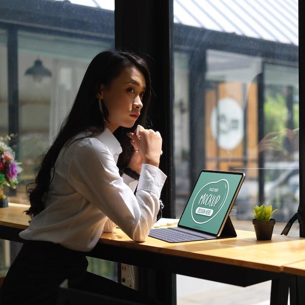 Bijgesneden schot van doordachte vrouwelijke kantoormedewerker zitten met mock-up digitale tablet Premium Psd
