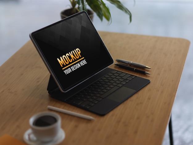 Bijgesneden schot van mock-up digitale tablet met toetsenbord, koffiekopje en pennen op houten tafel Premium Psd