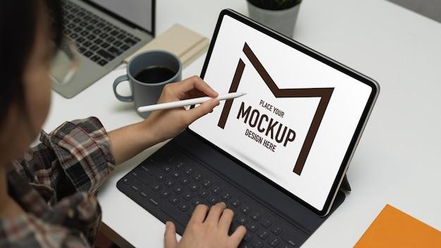 Bijgesneden schot van vrouwelijke werken met mock-up digitale tablet Premium Psd