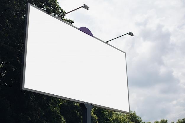 Bilbard met veelkleurige reclame en verlichting staat op straat bij daglicht, foto hieronder Gratis Psd
