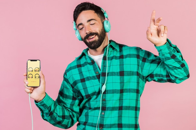 Blije jonge man met een koptelefoon en mobiele telefoon mock up Gratis Psd