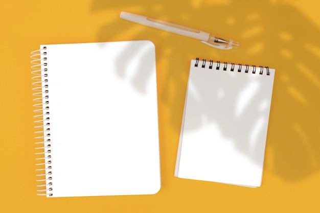Blocco note vista dall'alto su sfondo giallo, modello, creatore di scene Psd Premium
