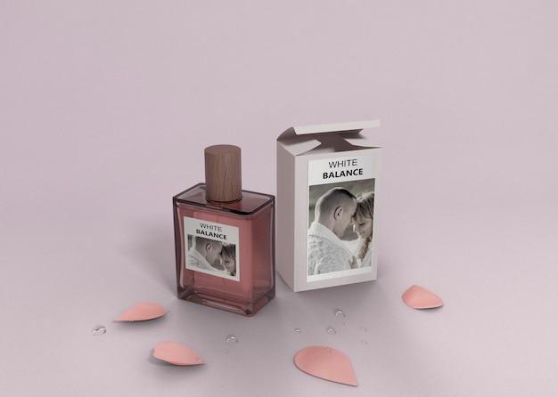 Bloemblaadjes en parfumfles op tafel Gratis Psd