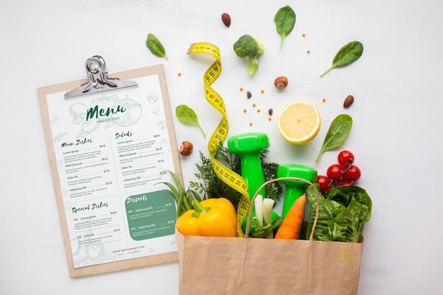 Bolsa de papel llena de deliciosos alimentos orgánicos y menú dietético PSD gratuito