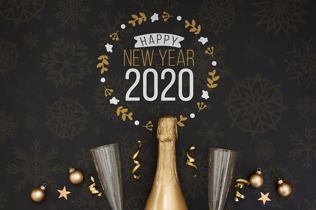 Botella de champán dorado y copas vacías sobre fondo negro PSD gratuito