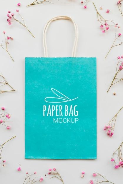 Bovenaanzicht assortiment van bloemen en papieren zakken Gratis Psd