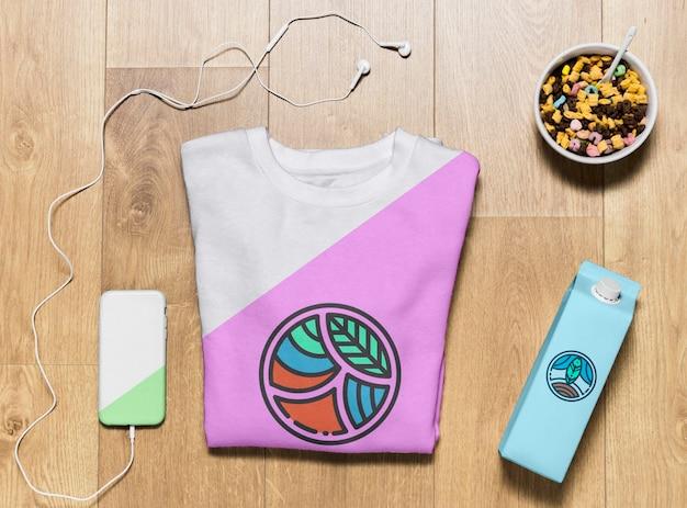 Bovenaanzicht gevouwen hoodie mock-up met telefoonhoes en snack Gratis Psd