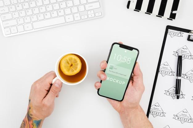 Bovenaanzicht handen met smartphone mock-up en thee Gratis Psd