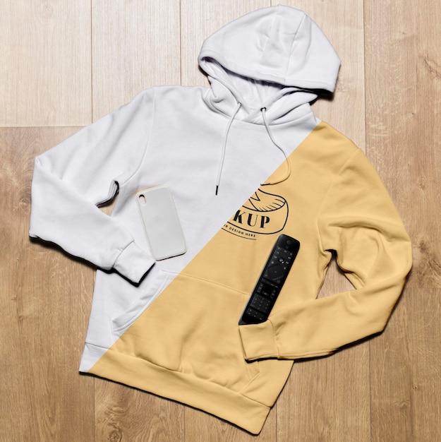 Bovenaanzicht hoodie mock-up met telefoonhoes en tv-afstandsbediening Gratis Psd