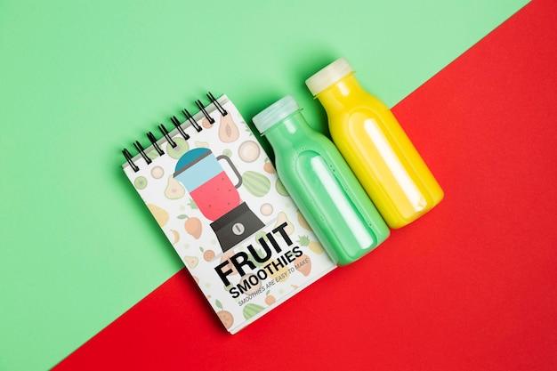 Bovenaanzicht kladblok en flessen met fruit smoothie Gratis Psd