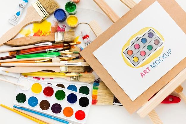 Bovenaanzicht kunstenaarsbureau met canvas standaard Gratis Psd