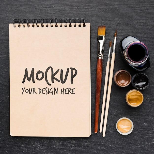 Bovenaanzicht notebook en penselen mock-up Gratis Psd