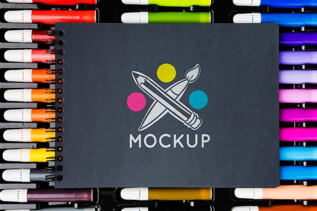 Bovenaanzicht notitieboekje op kleurrijke markeringen Gratis Psd