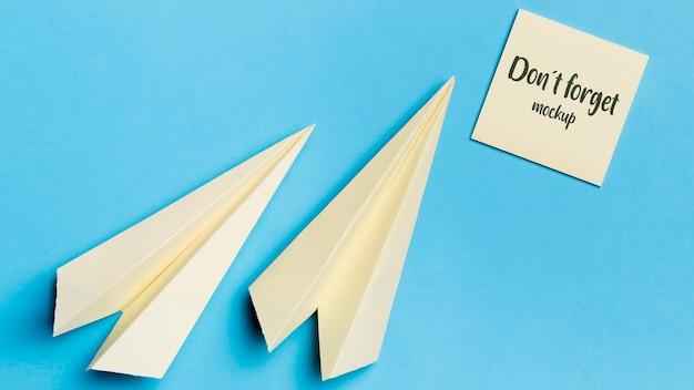 Bovenaanzicht papieren vliegtuig en notitie met mock-up Gratis Psd