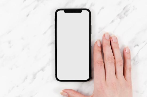 Bovenaanzicht smartphone mock-up met hand Gratis Psd