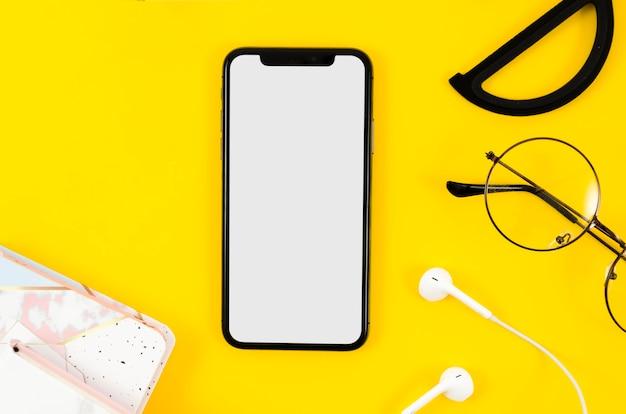 Bovenaanzicht smartphone mock-up met koptelefoon en bril Gratis Psd