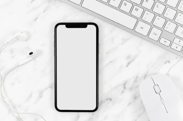 Bovenaanzicht smartphone mock-up met oortelefoons en muis Premium Psd
