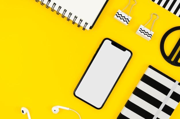 Bovenaanzicht telefoonmodel met kladblok en oortelefoons Gratis Psd