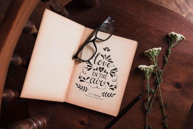 Bovenaanzicht van boek met glazen en bloemen in de stoel Gratis Psd