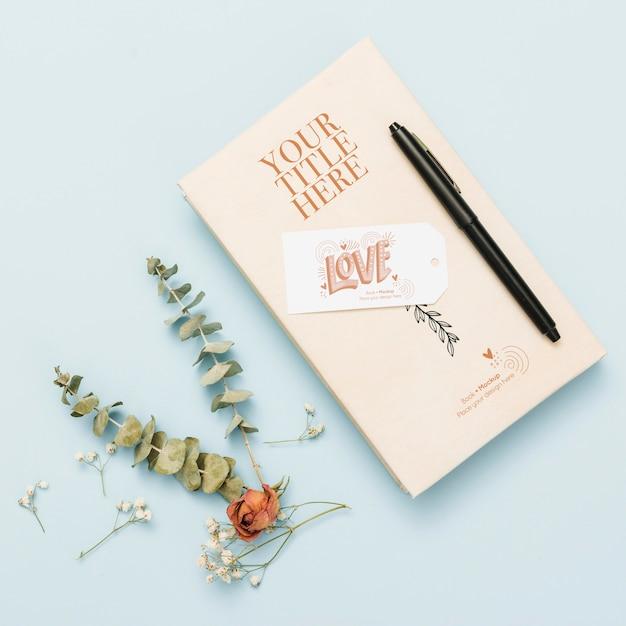 Bovenaanzicht van boekmodel met pen en bloemen Gratis Psd