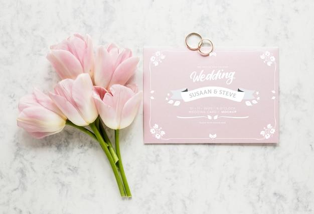 Bovenaanzicht van bruiloft kaart met boeket tulpen en ringen Gratis Psd