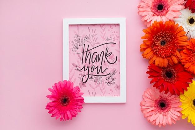 Bovenaanzicht van frame en bloemen met roze achtergrond Gratis Psd
