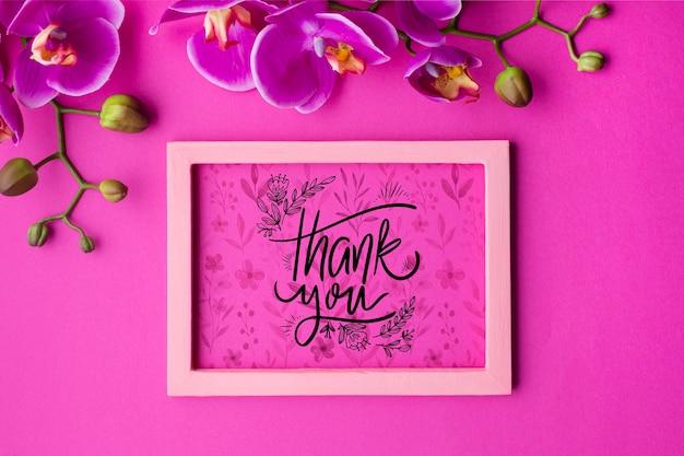 Bovenaanzicht van frame en bloemen op roze achtergrond Gratis Psd