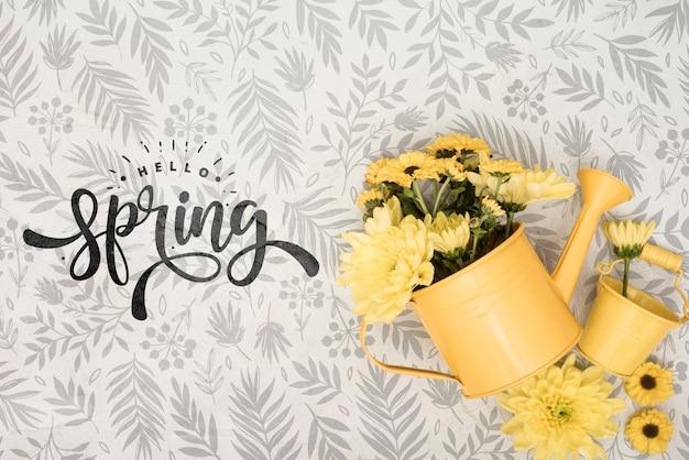 Bovenaanzicht van gele lentebloemen in gieter Gratis Psd