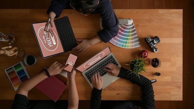 Bovenaanzicht van het ontwerpteam dat samen aan hun project werkt met mockup van digitale apparaten Premium Psd
