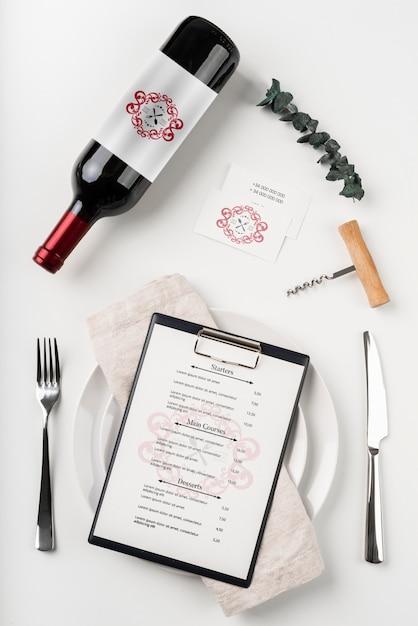 Bovenaanzicht van menu met fles wijn en bestek Gratis Psd