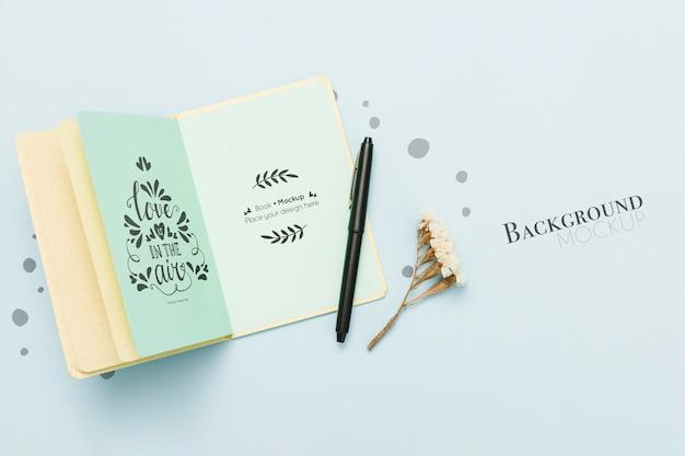 Bovenaanzicht van open boek met pen en bloemen Gratis Psd
