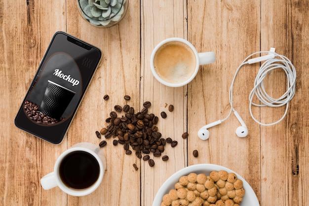 Bovenaanzicht van smartphone met koffiebonen en kopje thee Gratis Psd
