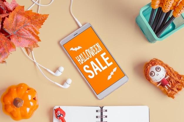 . bovenaanzicht van smartphone op kantoor bureau tafel met halloween accessoires. Premium Psd