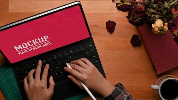 Bovenaanzicht van vrouwelijke handen typen op tablet mockup op houten tafel Premium Psd