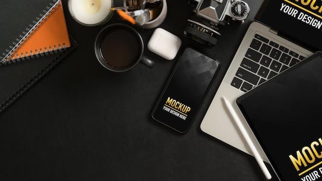 Bovenaanzicht van werktafel met mock-up smartphone, tablet, laptop, benodigdheden en kopieerruimte Premium Psd