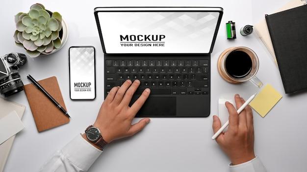 Bovenaanzicht van zakenman hand werken met tablet, smartphone mockup en kantoorbenodigdheden Premium Psd