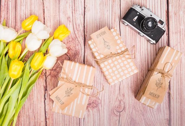 Bovenaanzicht verjaardag presenteert met bloemen en camera Gratis Psd