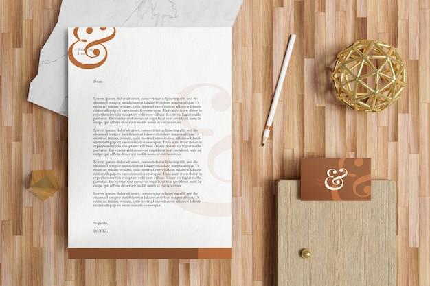 Briefhoofd a4-document met visitekaartje en briefpapiermodel in houten vloer Premium Psd