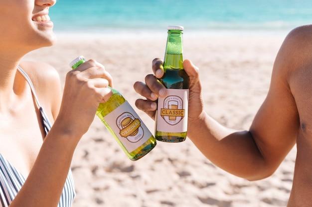 Brindando con dos botellas de cerveza en la playa PSD gratuito