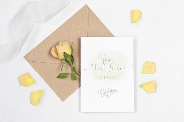 Carta di invito mockup con busta, rosa e petali Psd Premium