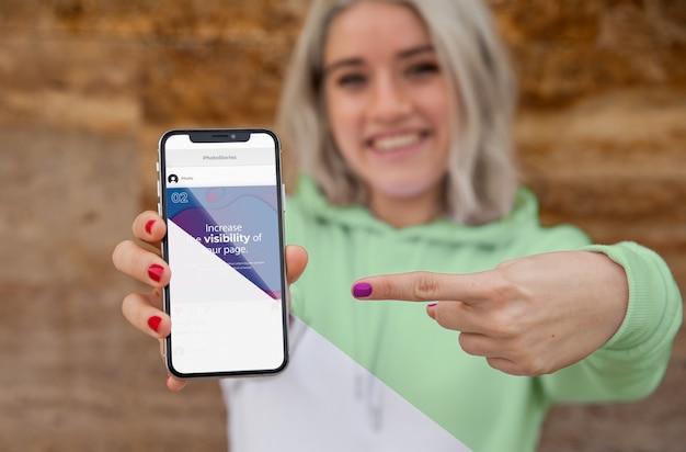 Chica con capucha apuntando al móvil PSD gratuito