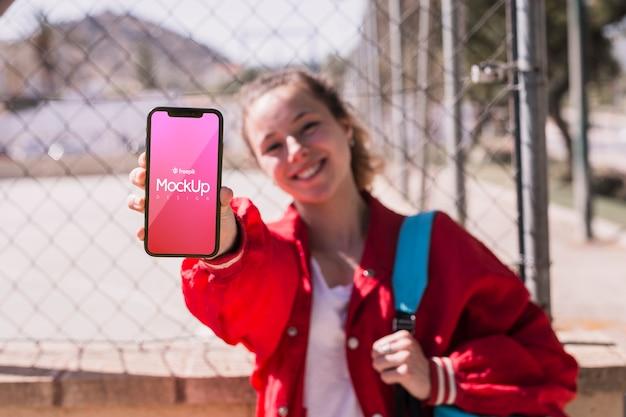 Chica estudiante mostrando su maqueta de teléfono PSD gratuito