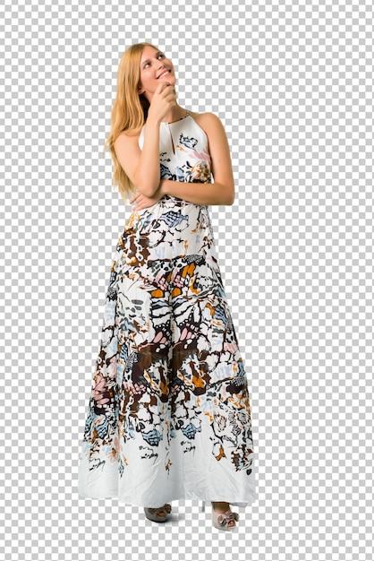 Chica joven rubia en un vestido del verano que se coloca y que piensa una idea mientras que mira para arriba PSD Premium