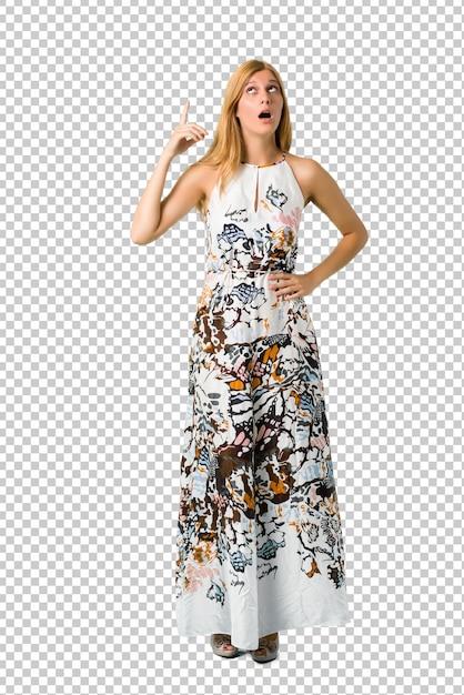 Chica joven rubia en un vestido del verano que se coloca y que piensa una idea que destaca el finger PSD Premium