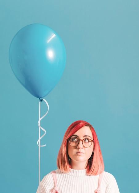 Chica de pelo rosa con un globo PSD gratuito