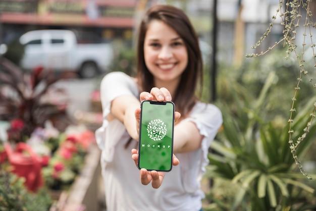 Chica sujetando mockup de smartphone con concepto de jardinería PSD gratuito