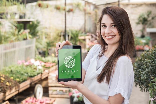 Chica sujetando mockup de tableta con concepto de jardinería PSD gratuito