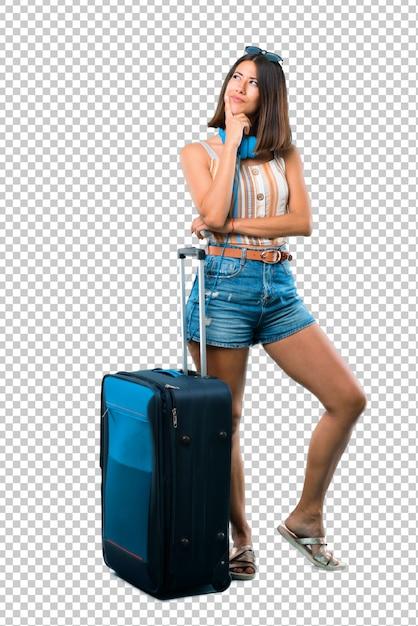 Chica viajando con su maleta de pie y pensando una idea mientras mira hacia arriba PSD Premium