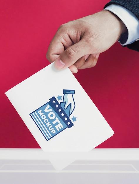 Close-up mannetje dat stembiljetmodel in doos aanbrengt Gratis Psd