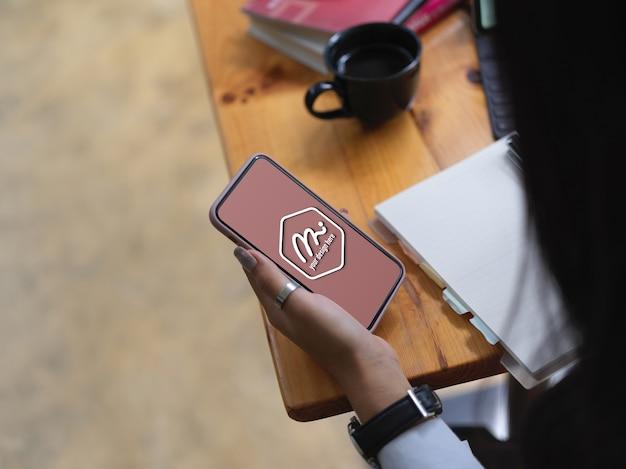 Close-up op handen met mockup van smartphonescherm Premium Psd
